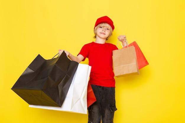 Widok z przodu małego uroczego kuriera w czerwonych t-shirtach z czerwonymi jeansami z czapką, przedstawiający kolorowe opakowania na zakupy
