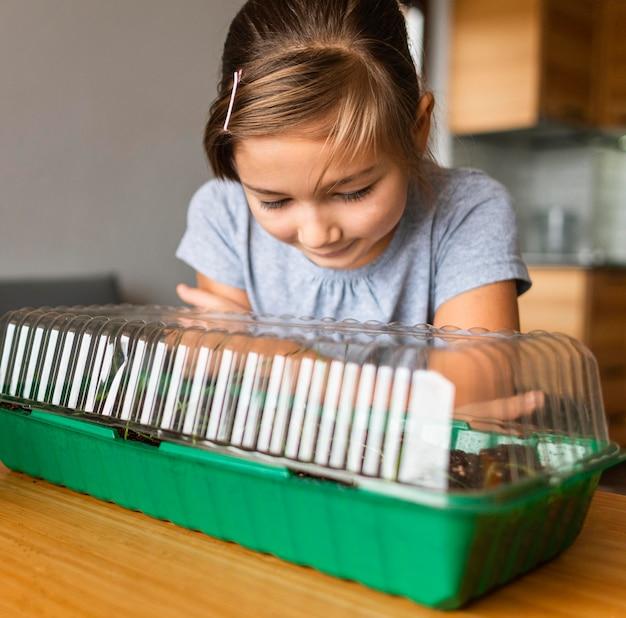 Widok z przodu małej dziewczynki obserwującej uprawy w domu
