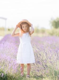 Widok z przodu małej dziewczynki ubranej w białą sukienkę, zakładającej słomkowy kapelusz, patrzącej na kamerę