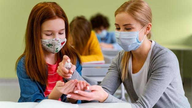 Widok z przodu małej dziewczynki z maską medyczną otrzymującą od nauczyciela środek dezynfekujący do rąk