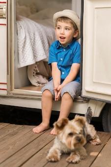 Widok z przodu mały chłopiec siedzi na przyczepie kempingowej obok uroczego psa
