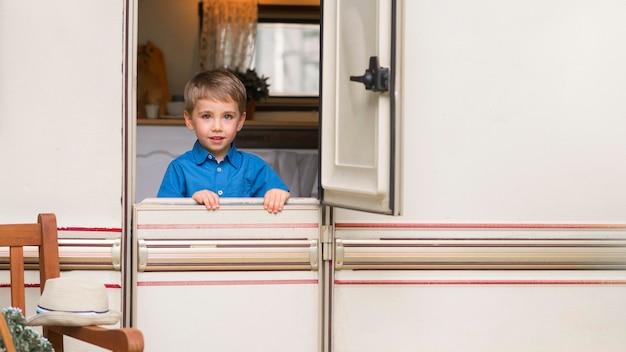 Widok z przodu mały chłopiec stojący przed drzwiami przyczepy kempingowej