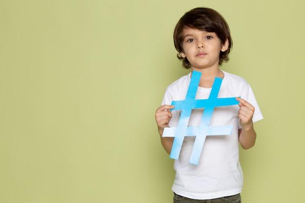 Widok z przodu mały chłopiec w białej koszulce z niebieskim znakiem na kamiennej przestrzeni