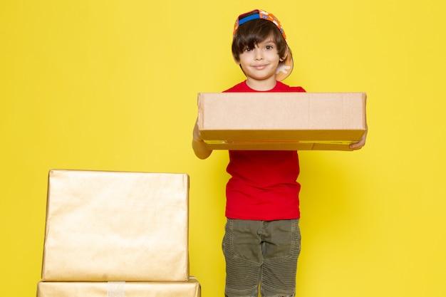 Widok z przodu mały chłopiec w czerwonej koszulce w kolorowe czapki i spodnie w kolorze khaki, trzymając pudełka na żółtym tle