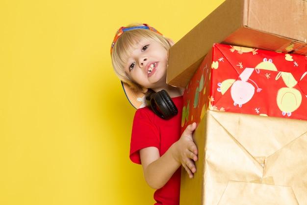 Widok z przodu mały chłopiec w czerwonej koszulce w kolorowe czapki i szare dżinsy gospodarstwa pudełko na żółtym tle