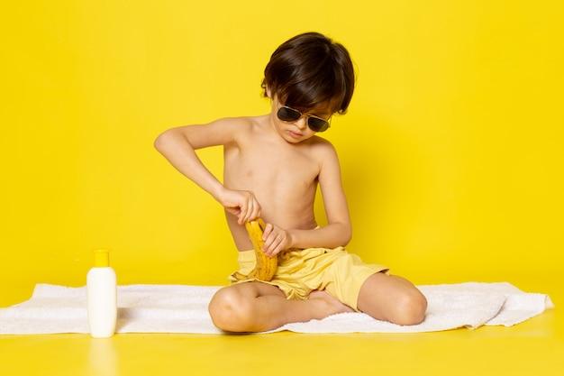 Widok z przodu mały chłopiec w okularach przeciwsłonecznych obieranie banana na żółto