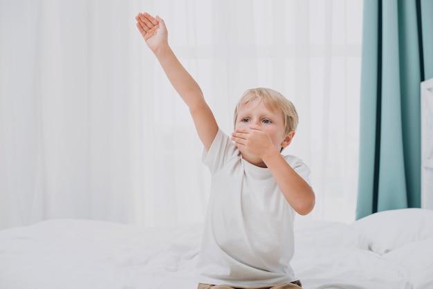 Widok z przodu mały chłopiec ziewanie po przebudzeniu