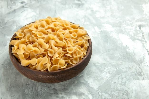 Widok z przodu mały surowy makaron wewnątrz talerza na jasnym zdjęciu wiele mączek w kolorze ciasta