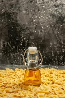 Widok z przodu mały surowy makaron z olejem na ciemnym wielu cieście jedzenie posiłek kolor zdjęcie włoski makaron