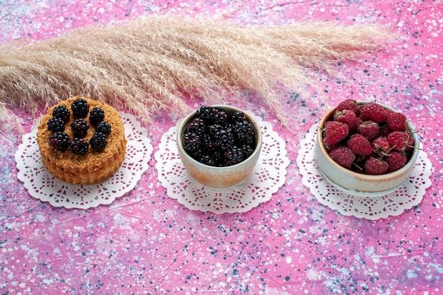 Widok z przodu mały tort jeżynowy z malinami i świeżymi jeżynami na jasnoróżowym tle.
