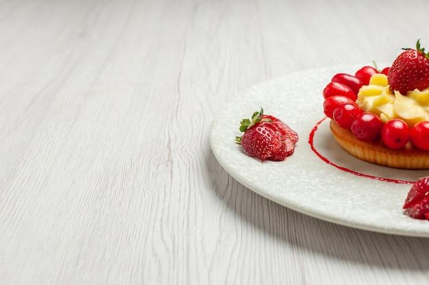 Widok z przodu mały tort z owocami wewnątrz talerza na białym biurku ciasto deserowe owoce