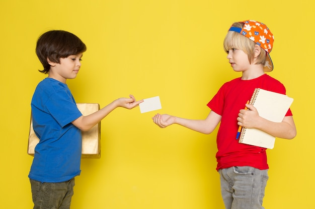 Widok z przodu małych chłopców w czerwonych i niebieskich t-shirtach kolorowych czapkę i szare dżinsy gospodarstwa pudełko na żółtym tle