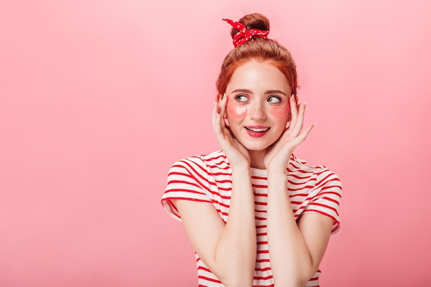 Widok z przodu marzycielskiej rudej dziewczyny z opaskami na oku. ładna kobieta w t-shirt w paski robi rutynowej pielęgnacji skóry na białym tle na różowym tle.