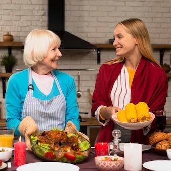 Widok z przodu matki i córki, trzymając jedzenie i patrząc na siebie