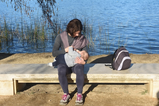 Widok z przodu matki ubranej w sportową karmiącą swoje dziecko piersią