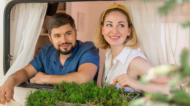 Widok z przodu mąż i żona patrząc przez okno przyczepy kempingowej