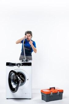 Widok z przodu mechanika w mundurze stojącego za pralką, wskazującego na rurę na białej ścianie