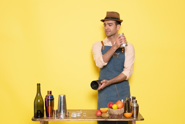 Widok z przodu męski barman pracujący z shakerami i robiący drinka na żółtej ścianie noc mężczyzna pije alkoholowy klub barowy