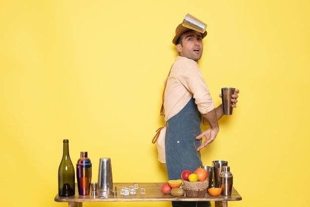 Widok z przodu męski barman pracujący z shakerami i robiący drinka na żółtej ścianie nocny męski drink alkoholowy klub barowy