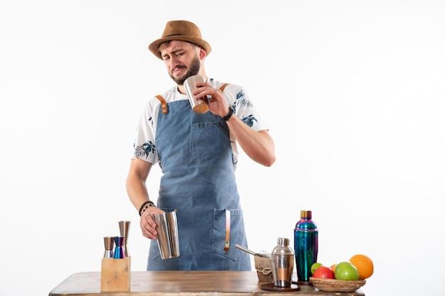 Widok z przodu męski barman przed biurkiem barowym przygotowujący drinka pracujący z shakerem na białej ścianie bar alkohol praca klub nocny drink