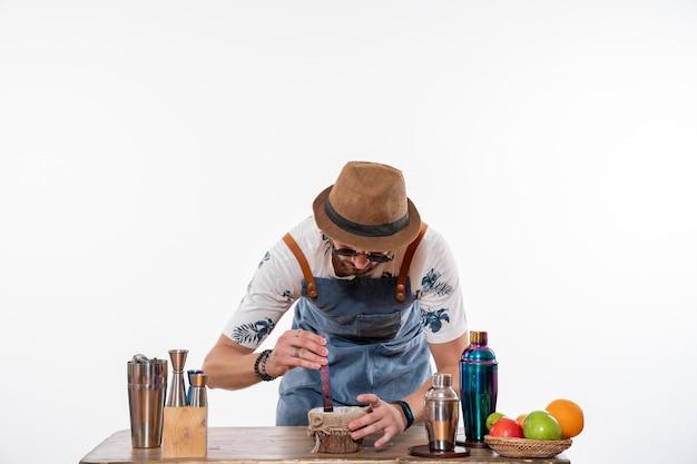 Widok z przodu męski barman przed biurkiem barowym przygotowujący napój na białej ścianie bar alkohol praca klub nocny drink