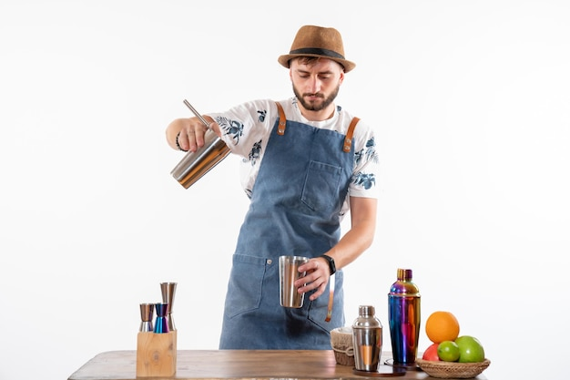 Widok z przodu męski barman przed biurkiem barowym przygotowujący napój w shakerze na białej ścianie bar alkohol praca nocna owoce klub napojów