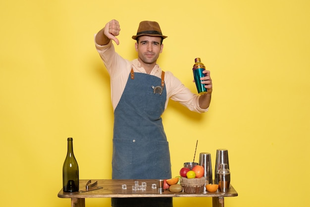 Widok z przodu męski barman przed stołem z napojami i shakerami na żółtej ścianie nocny alkohol męski klubowy napój barowy