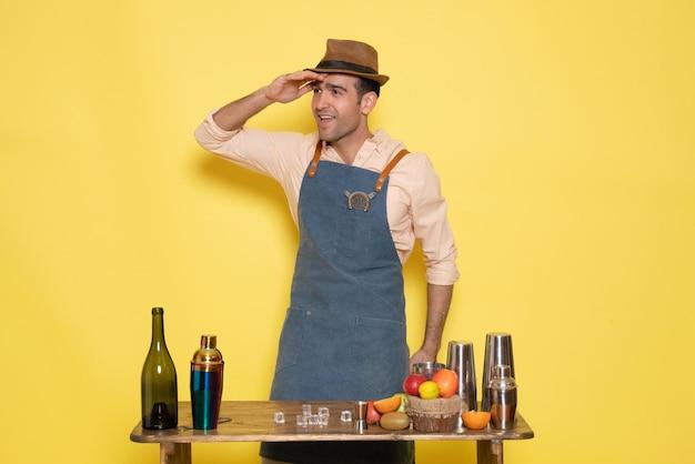 Widok z przodu męski barman przed stołem z napojami i shakerami na żółtej ścianie pije nocny alkoholowy bar klubowy męski