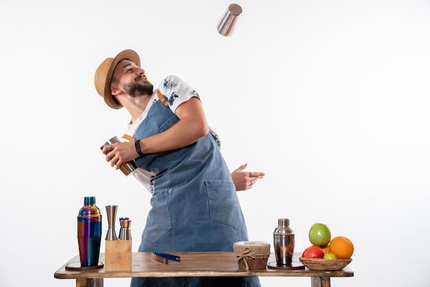 Widok z przodu męski barman robi drinka i pracuje z shakerami na białej ścianie nocny bar alkoholowy drink praca