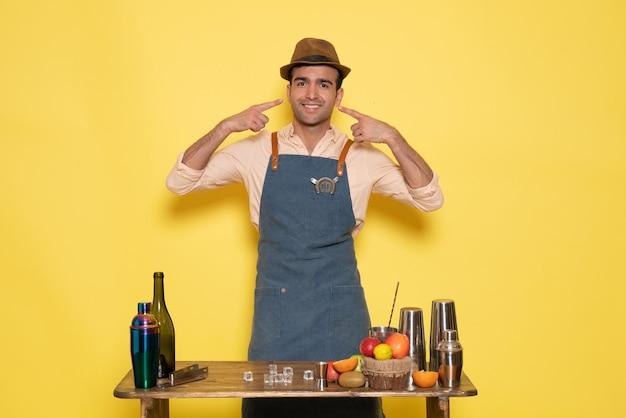 Widok z przodu męski barman stojący przed biurkiem z napojami i owocami uśmiechający się na żółtej ścianie pić klub nocny sok bar męski