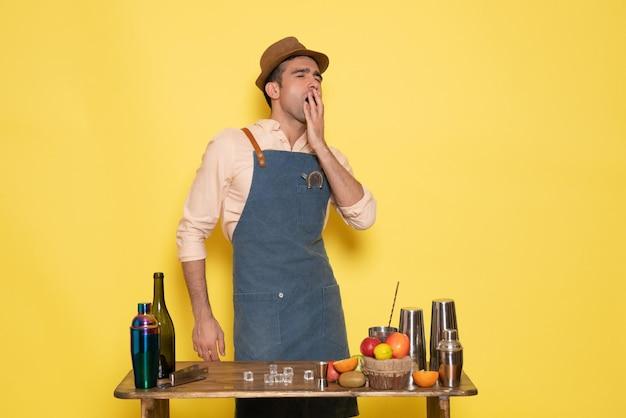 Widok z przodu męski barman stojący przed biurkiem z napojami i owocami ziewającymi na żółtej ścianie drink bar klub nocny sok