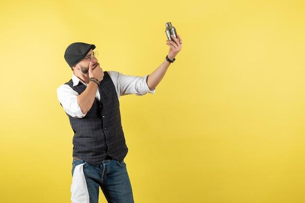 Widok z przodu męski barman trzymający mały srebrny shaker na żółtej ścianie model pić klub pracy mężczyzna nocna praca