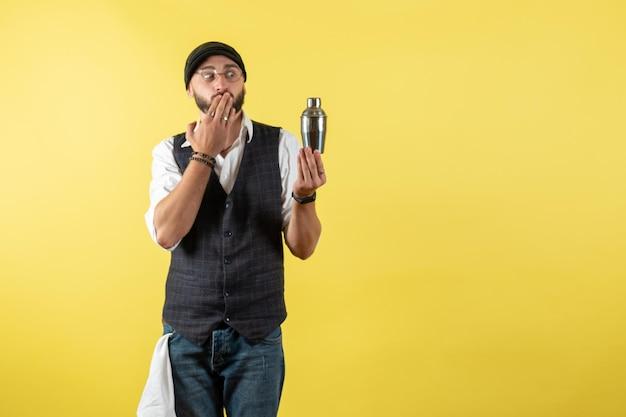 Widok z przodu męski barman trzymający mały srebrny shaker na żółtej ścianie model pić praca praca klub męski noc