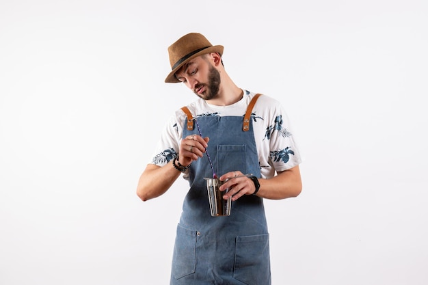 Widok z przodu męski barman trzymający shaker na białej ścianie nocny klub alkoholowe napoje kolorowe paski