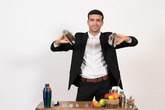 Widok z przodu męski barman w garniturze pracujący z shakerami i robiący drinka na białej ścianie męski klub nocny dance drink bar