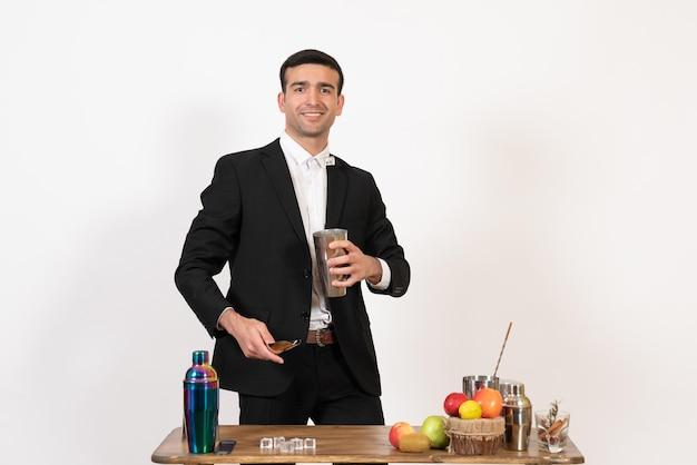 Widok z przodu męski barman w garniturze pracujący z shakerami i robiący drinka na białym biurku męski klub nocny dance drink bar
