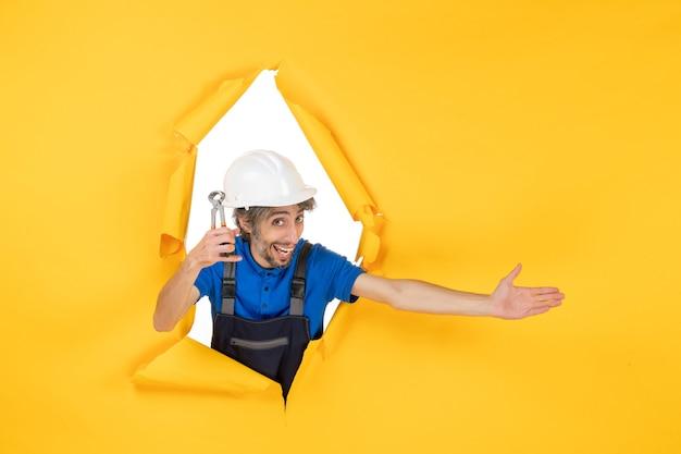 Widok z przodu męski budowniczy trzymający szczypce na żółtym tle
