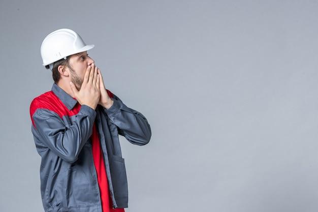 Widok z przodu męski budowniczy w mundurze i kasku na jasnym tle
