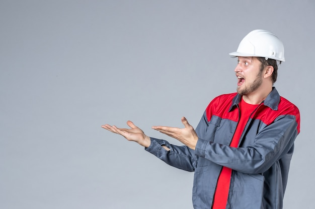 Widok z przodu męski budowniczy w mundurze i kasku na szarym tle