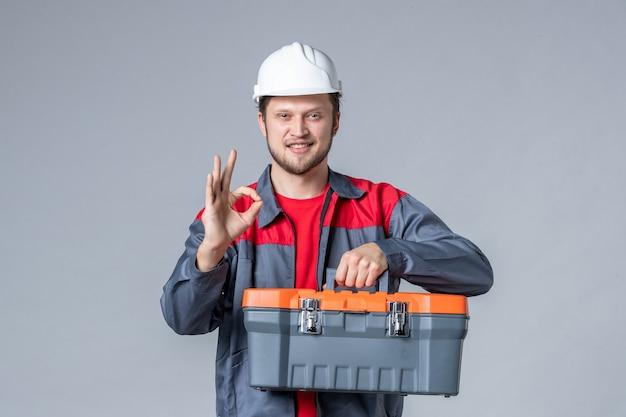 Widok z przodu męski budowniczy w mundurze i kasku trzymającym walizkę narzędziową na szarym tle