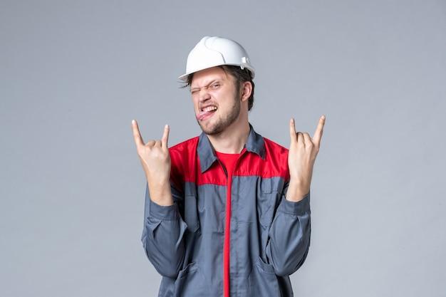 Widok z przodu męski budowniczy w mundurze i kasku w pozie rocker na szarym tle