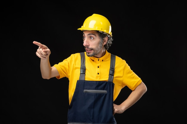 Widok z przodu męski budowniczy w mundurze na czarnej ścianie
