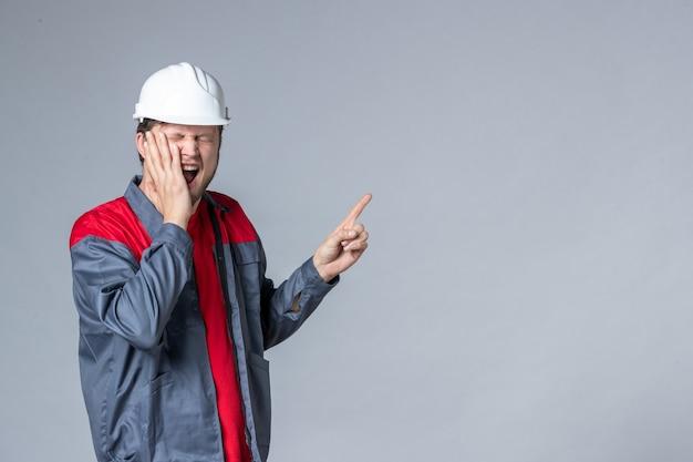 Widok z przodu męski budowniczy w mundurze na jasnym tle