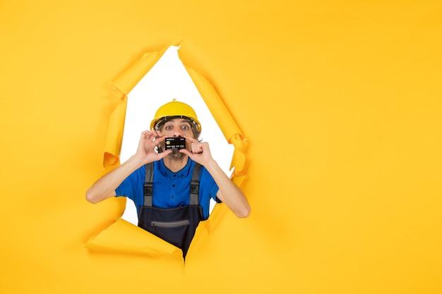 Widok z przodu męski budowniczy w mundurze trzymający czarną kartę bankową na żółtym tle