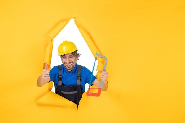 Widok z przodu męski budowniczy w mundurze trzymającym piłę łukową na żółtym tle
