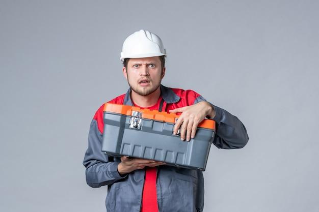 Widok z przodu męski budowniczy w mundurze trzymającym walizkę narzędziową na szarym tle