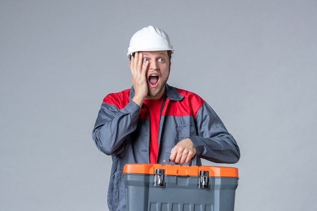 Widok z przodu męski budowniczy w mundurze trzymającym walizkę narzędziową z podekscytowaną twarzą na szarym tle