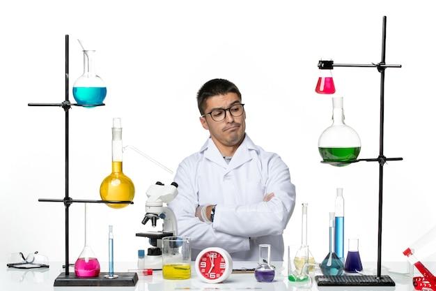 Widok z przodu męski chemik w białym garniturze medycznym siedzi i przygotowuje się do pracy na białym tle wirusy naukowe - laboratorium pandemiczne