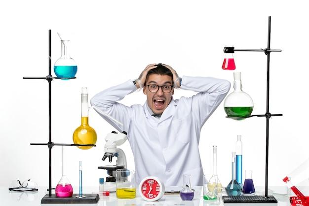 Widok z przodu męski chemik w białym garniturze medycznym siedzi i robi śmieszne miny na białym tle wirus science covid- pandemic lab