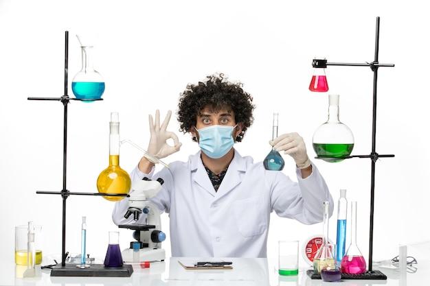 Widok z przodu męski chemik w białym kombinezonie medycznym iz maską trzymającą niebieski roztwór na jasnobiałej przestrzeni